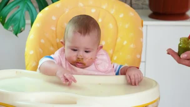Kis anya baba táplálja püré gyümölcsök zöldségek. szelektív fókusz