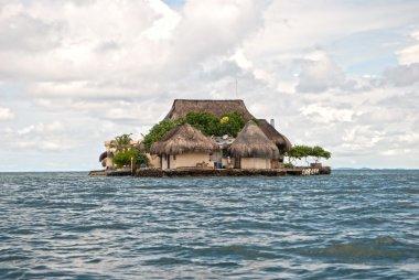 Bungalows on green island in ocean