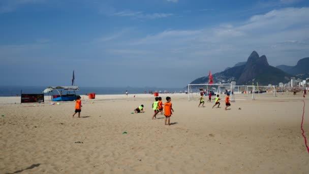 Děti hrají fotbal na pláži
