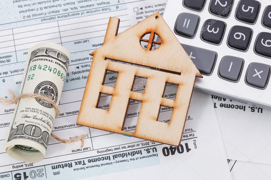 Dinero y casa de madera con calculadora de impuesto sobre la forman ...