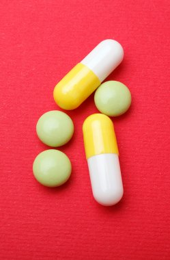 pills and capsules on red background