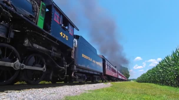 Strasburg, Pennsylvania, July 2020 - Low Angle View of an Approaching Steam Engine Blowing Smoke and Steam on a Sunny Summer Day