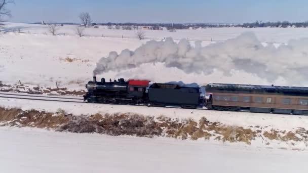 Letecký pohled na starodávnou parní lokomotivu přibližující se k tažným osobním autům a foukající kouř a páru po sněhové bouři