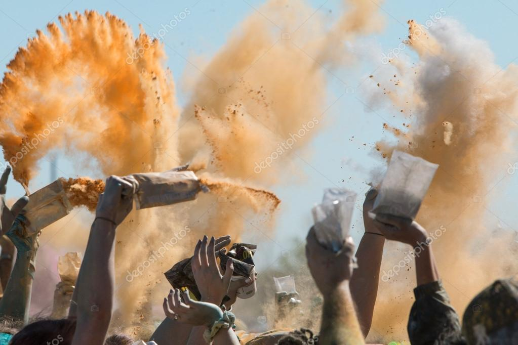 hands throw packets of colored corn starch at color run stock photo - Color Packets