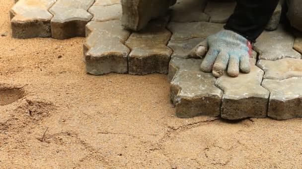 Dělník, instalaci starých dlážděných blok pro sestavení podlahy zem