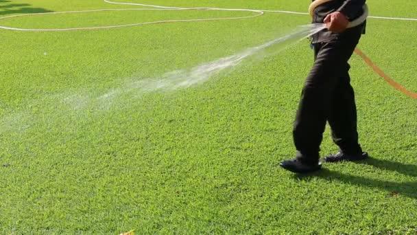 Mann am schönen grünen Rasen Bewässerung
