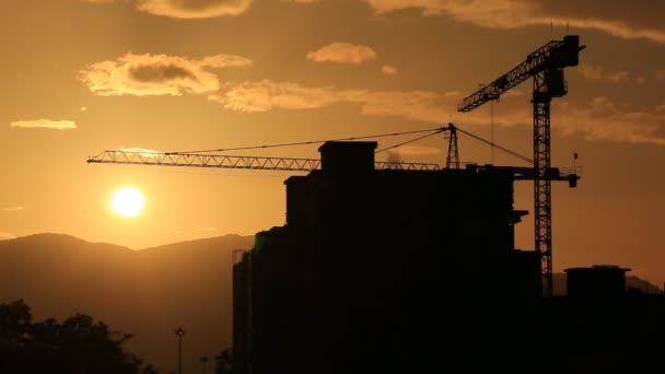 time lapse silhouette crane working in construction site and sunset