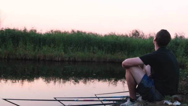 4k. Calm relaxed man fishes on a lot of fishing rods while sitting on the shore of the lake at sunset