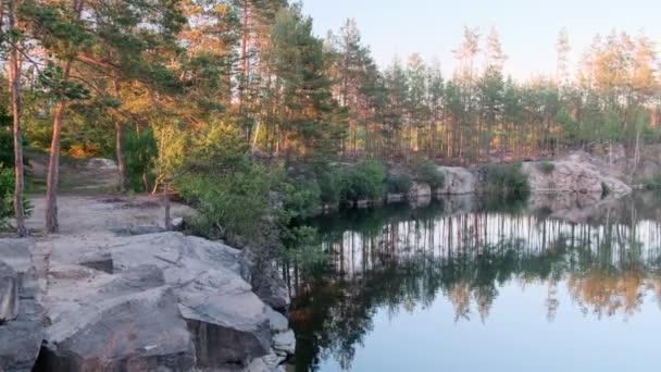 Kilátás egy gyönyörű elárasztott gránit kőbánya kék vízzel egy fenyőerdő között egy napsütéses nyári napon, 4k