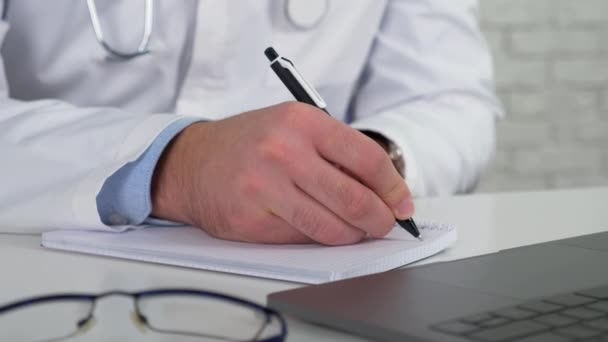Doctor examines patient online video call laptop writes symptoms in notebook