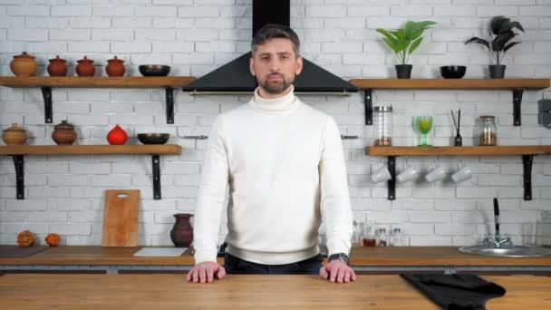Portrét vážný kuchař muž v bílém svetru hledá fotoaparát doma kuchyně