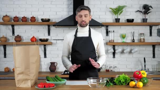 Mosolygós férfi szakács kötény üdvözöl mondja rekordok online webinar otthon konyha
