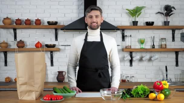 Usmívající se kuchař muž v zástěře stojící u stolu s potravinovou zeleninou připraven vařit