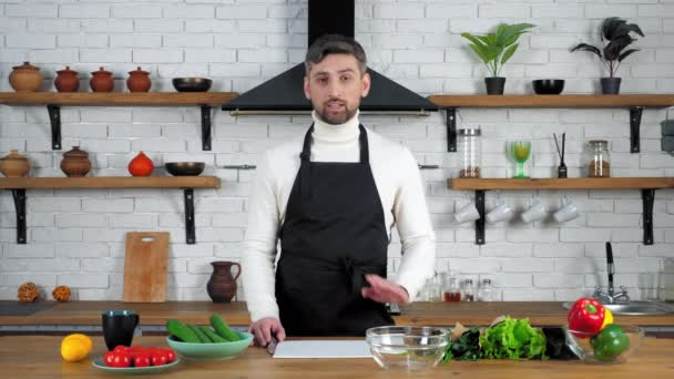Man chef in apron in home kitchen listens online student question tells teaches