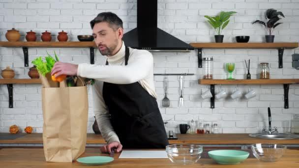 Mosolygó ember séf üdvözöl mondja eltávolítja a zöldségeket papírzacskó elkészítéséhez élelmiszer