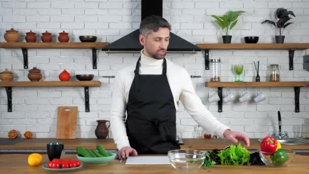 Muž kuchař v kuchyni říká, učí hospodyňky ukazuje ingredience pro vaření salát