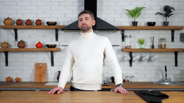 Töprengő férfi áll otthon konyha közelében asztal néz fel nyitott szájjal