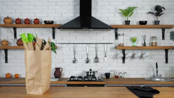 Black apron and paper bag with vegetables for cooking salad stands on table