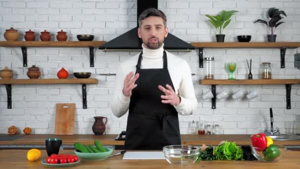 Muž kuchař v černé zástěře říká, učí online video kulinářské webinář v kuchyni