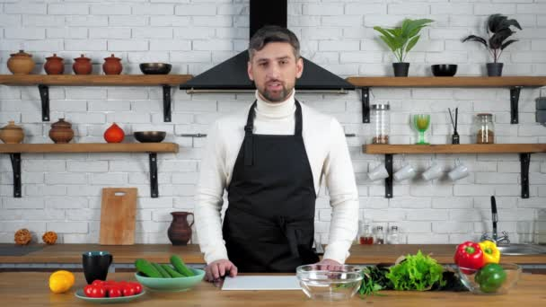 Muž kuchař kuchař v kuchyni pozdravuje ukazuje ingredience pro vaření salát