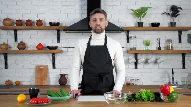 Muž kuchař v zástěře učí hospodyňky online video kulinářské webinář v kuchyni