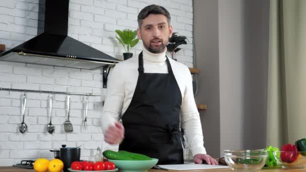 Man chef élelmiszer blogger kötény üdvözöl tanít online videokamera webkamera a konyhában