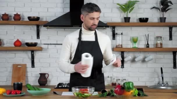 Usmívající se muž kuchař v zástěře utírá ruce s papírovým ručníkem doma moderní kuchyně