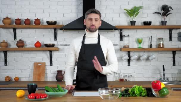 Usmívající se muž kuchař v zástěře vypráví záznamy online video kulinářské webinář v kuchyni