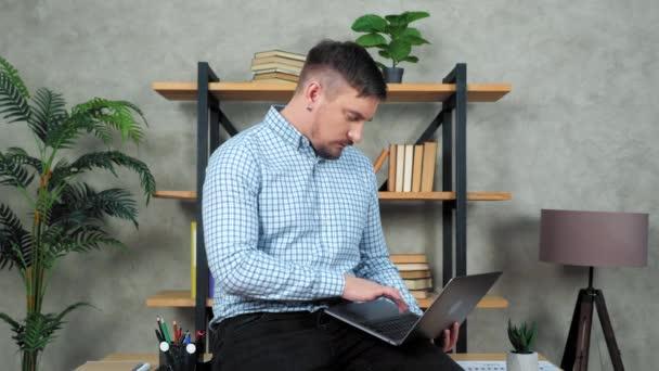 Podnikatel sedí za stolem v kanceláři používá notebook psaní textu na klávesnici počítače