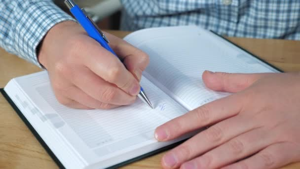 Close up businessman hands writes to-do list in notebook works at home office