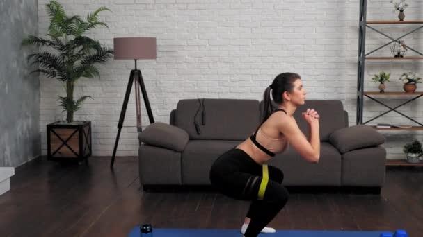 Krásná sportovní svalnatá dívka sportovkyně dělá squat cvičení s loop band