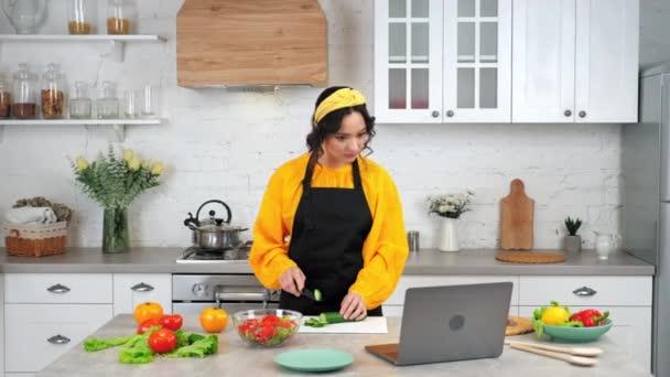 Frau in Küchenscheiben Gurke hören Koch online Kochkurs ansehen Laptop
