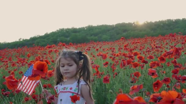 Americká holčička s americkou vlajkou. Den nezávislosti. Makové pole při západu slunce