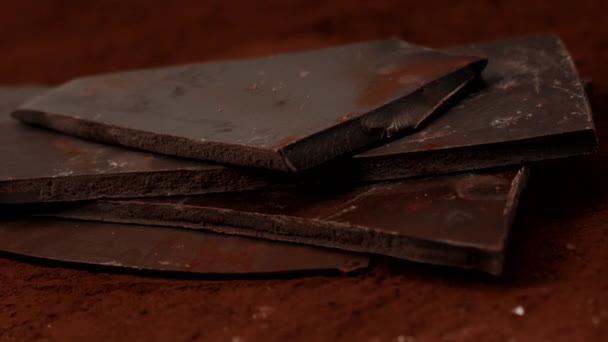 Hromada čokolády v kakaovém prášku roztříštěná bodavým detailem, zpomaleným pohybem