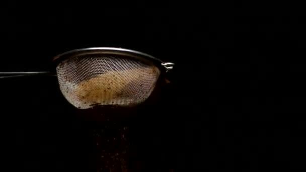 Posypání skořice káva čokoládové kakao prášek v pomalém mo, černé pozadí