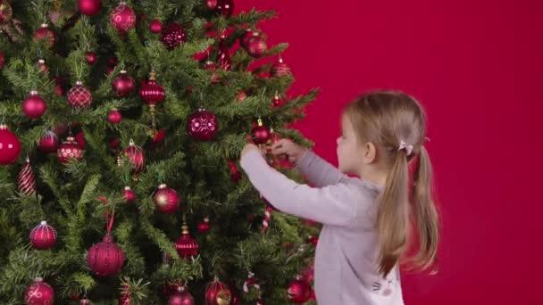 Kleines Mädchen schmückt Weihnachtsbaum, hängt schöne Weihnachtskugel, roter Hintergrund