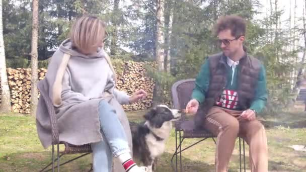 Beautiful woman and man sitting by campfire plays with dog having fun on picnic