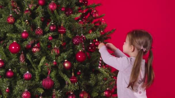 Malé roztomilé dítě zdobí vánoční stromek s vánoční cukrovou třtinou na červeném pozadí