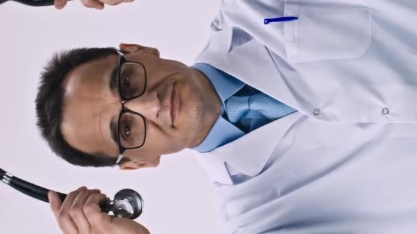 Vertical shot Handsome male doctor in medical coat puts on stethoscope and smiles