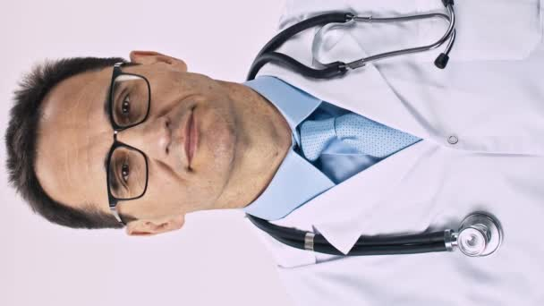 Vertical shot Middle aged doctor with snow-white smile pulls hand forward and shows a thumb