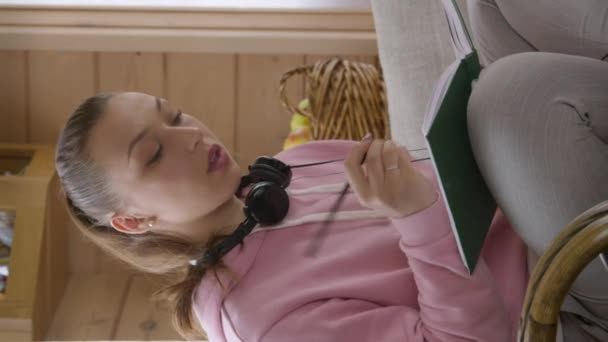Vertical shot Young caucasian student girl in pink hoodie studying at home during quarantine.