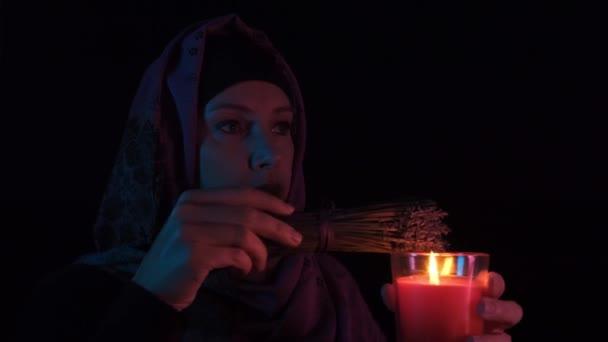 Noční portrét čarodějnice vrhající kouzlo na červenou svíčku a tvořící čarodějnictví se suchými bylinkami