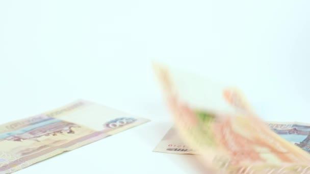 Orosz rubel csökkenő papírpénz, bankjegyek fehér háttérrel, lassított felvétel, sekély fókusz