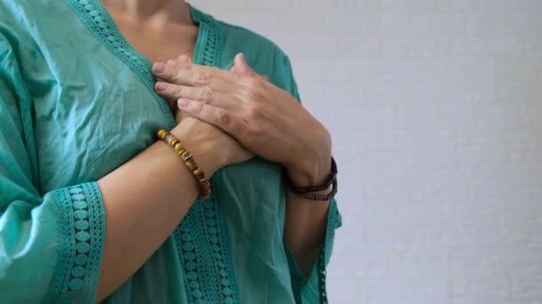 Dankbare Frau drückt Dankbarkeit mit Händen aus, Dame in grünem Ethno-Gewand bedankt sich mit Handgeste