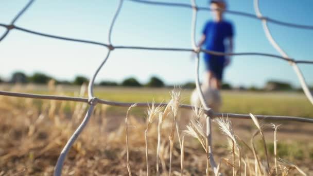 Fußballkonzept. Der Fußballer schießt den Ball ins Tor. Der Junge tritt den Ball. Straßensport in einer armen Gegend einer Stadt oder eines Dorfes. Ausbildung. Kindheitserinnerungen an einen Fußballstar.