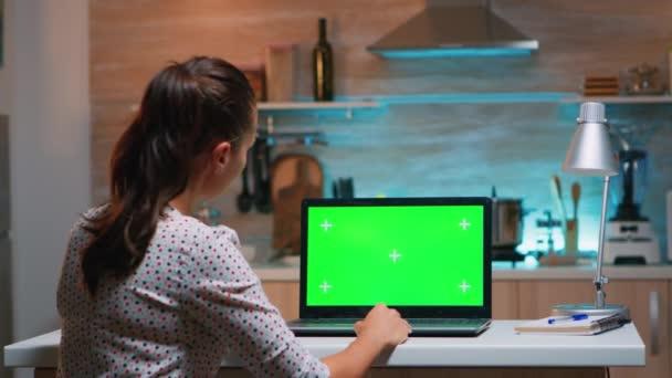 Obchodní žena při pohledu na zelené obrazovce notebook