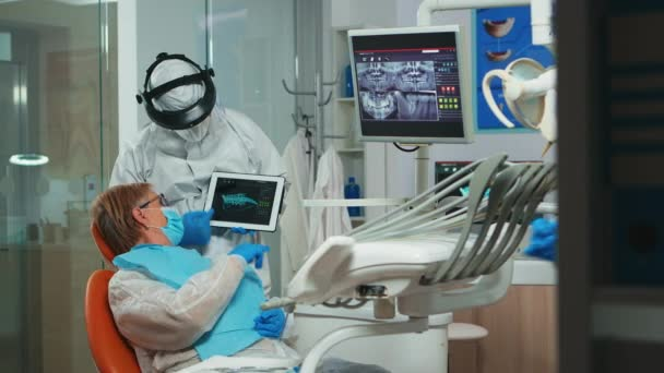 Kieferorthopäde im Overall mit Tablet erklärt Zahnröntgenbild