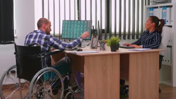 Gelähmter Finanzexperte sitzt im Rollstuhl und analysiert Wirtschaft