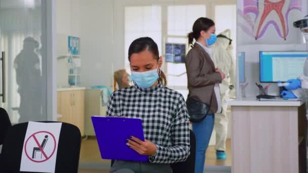 Frau mit Gesichtsschutzmaske schreibt auf Anmeldeformular