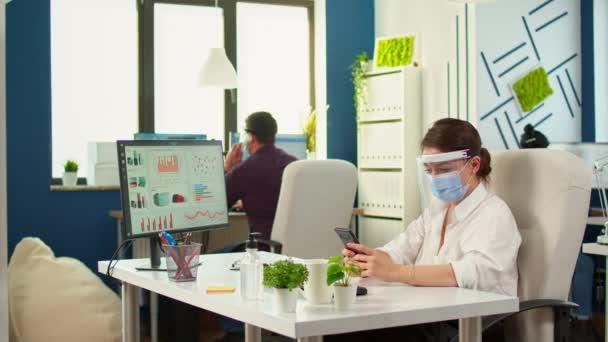 Unternehmer mit Schutzmaske tippt auf Handy